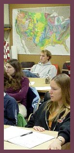 Students in class with map in background.