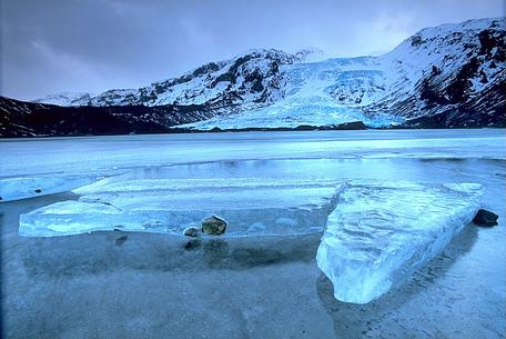 An icy lake with mountains in the background.