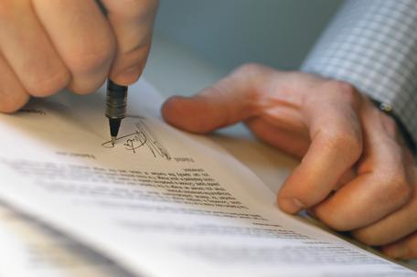 Hands holding a pen signing a document