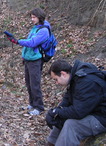 foreground student is resting while background student uses GPS receiver