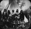 Crow tribe members in front of a teepee.