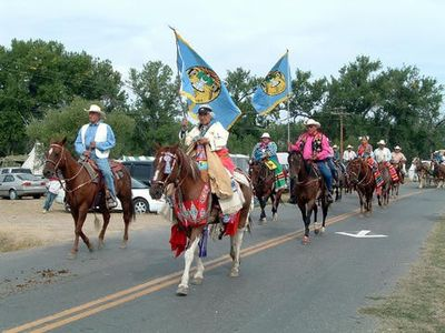 Pauline Small on horseback. She carries the flag of the Crow Tribe of Indians. As the first woman official, she is entitled to carry the flag during the Crow Fair Parade.