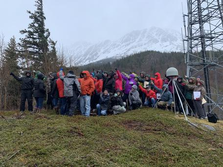 Workshop participants at GPS station AC20 near Girdwood, AK showing the direction of plate motion.