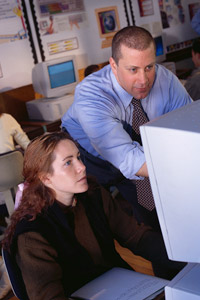 A teacher provides guidance and encouragement to a student in a computer assignment