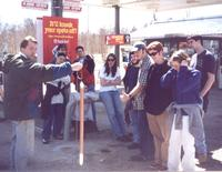 Hydrogeology field trip students admire a bailer full of gasoline drawn from a monitoring well at a gas station.