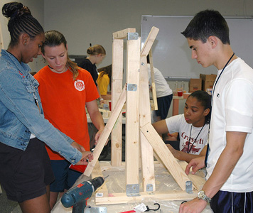 Students at a STEM seminar assemble a catapult