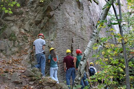 Students wearing hard hats stand under a vertical rock face showing ripples marks in Baraboo, WI.