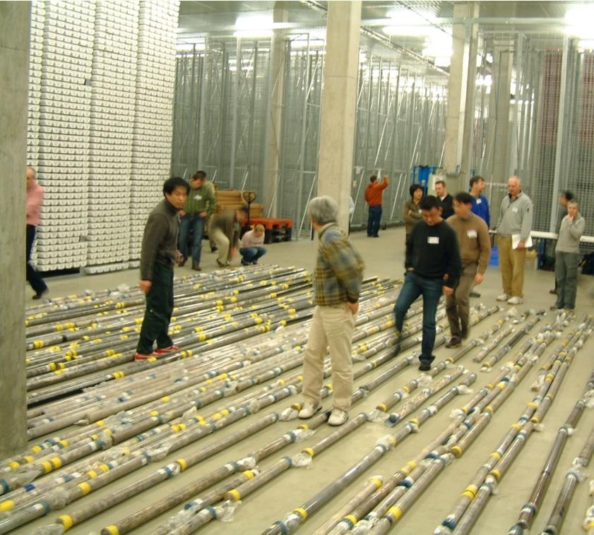 Scientists looking at a number of cores in a warehouse.