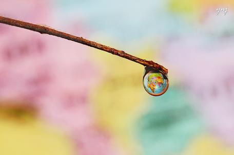Earth hanging on a water drop