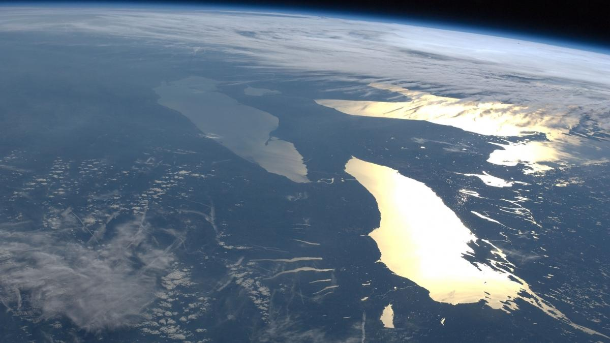 Clouds and sun glint off the Great Lakes as seen from the International Space Station (NASA).