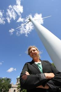 Former executive director of a green energy company stands in front of a wind turbine.