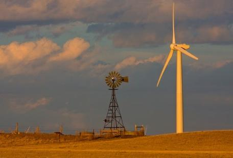 Old water pumping windmill and modern wind turbine