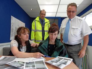 Representatives from multiple agencies survey flood damage.