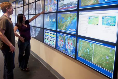 Students study the weather wall at Penn State