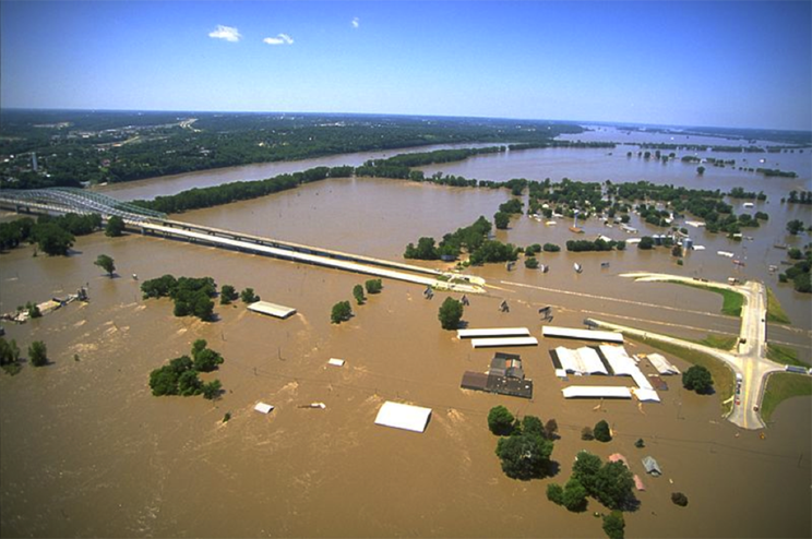 photograph showing multiple homes under water and a highway interchange that is partially under flood waters.