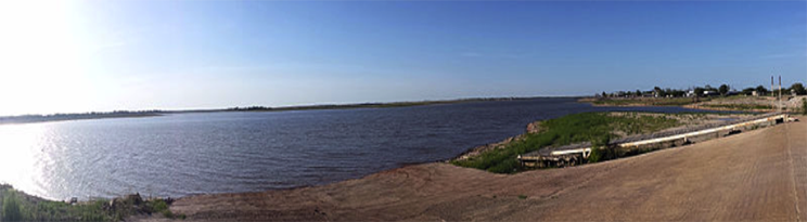 photograph showing a reservoir with water level well below the normal capacity.