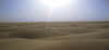 photograph showing the sky above barren sand dunes that fill the rest of the picture.