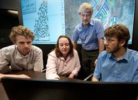 Students and NREL staff conducting at class at the Distributed Energy Systems Integration group's visualization center