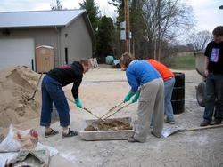 Eco-house students mixing plaster Carleton College