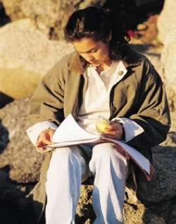 A student writes in a journal while sitting outdoors