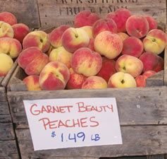 A crate of locally-grown peaches at a farmer's market.