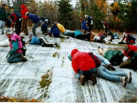 Students studying a striated rock in northern MN