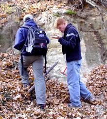 Decorative image showing students examining an outcrop.