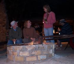 Image of field conference participants relaxing by the barbecue pit listening to music.