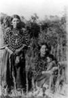 Crow women in traditional Elk tooth dresses, one sitting and holding a baby.