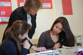 A teacher assisting students with an assignment