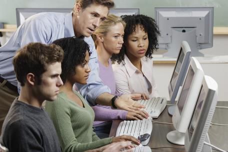 Professor assisting students with computer work